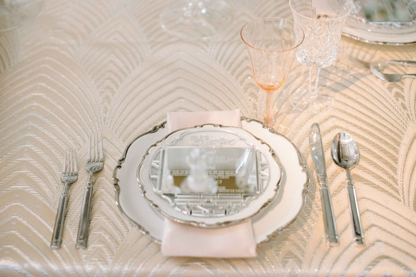 ornate china with silverware and engraved mirror as menu
