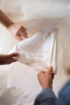 lace from mother of the bride's veil being added to daughter's wedding dress