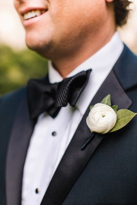 Close up of groom's tuxedo and white ranunculus boutonniere with green leaves