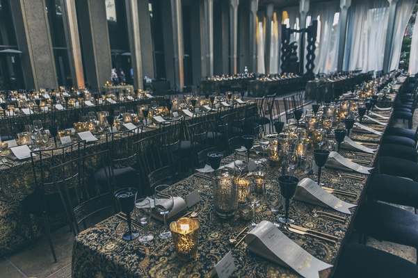 Draped tables in black and gold linens with only candlelight for an intimate dinner reception