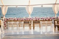 Wood tables head table with flower runner of roses in shades of white, pink, and burgundy by ocean