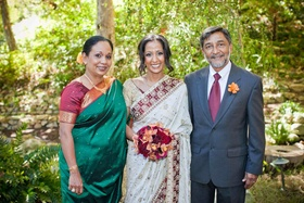 Bride in a white sari with burgundy and gold trim with parents