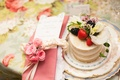 Sponge cake on flower print table with fresh pink roses and ribbon