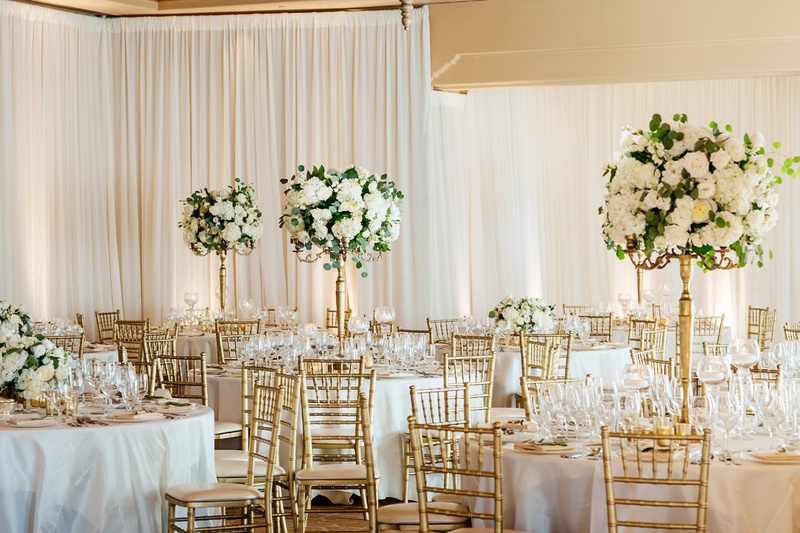the resort at pelican hill wedding reception with gold chiavari chairs, tall white centerpieces