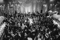Black and white photo of bride and groom doing hora jewish wedding reception tradition guests