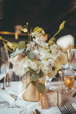 small floral centerpiece with white and blush flowers and eucalyptus in gold vase