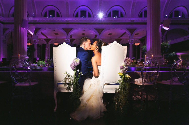 Bride and groom kiss at tall chairs with fresh flowers purple lighting kiss reception