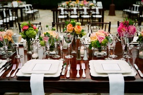 Wood table with bright flowers and scalloped chargers