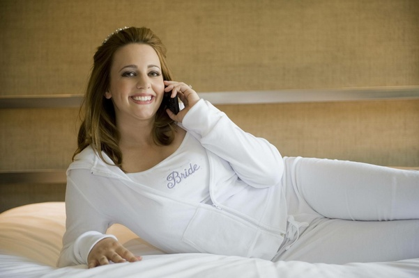 Bride on cell phone in white tracksuit and tank