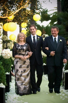 User walks mother of groom down garden ceremony aisle