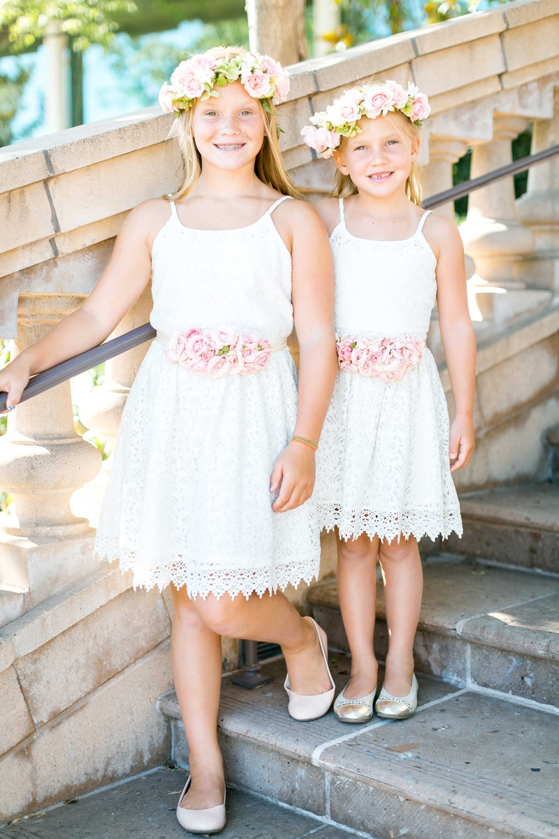 0e951881627 Two flower girls in matching white lace dresses with pink rose belt flower  crowns and flats
