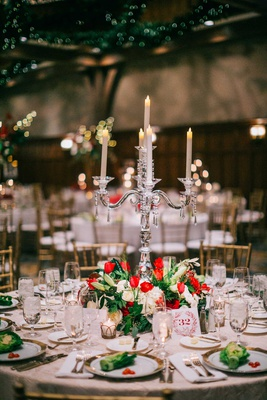 low centerpiece of white red flowers greenery with crystal candelabra lettuce on plates