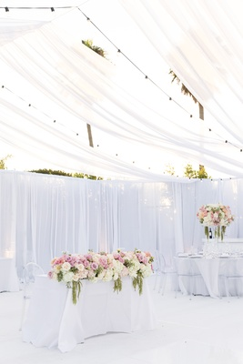 tented reception white space, sweetheart table fully covered with flowers