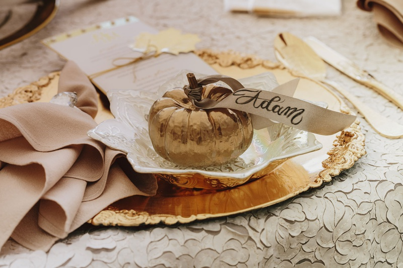 fall wedding ideas gold pumpkin with place card ribbon calligraphy gold charger plate