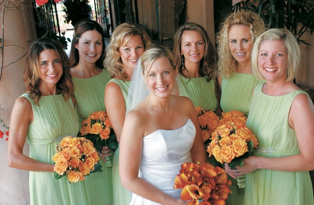Bride with bridesmaids in green gowns and holding orange flowers