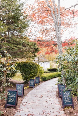corinthians passages in calligraphy on black chalkboards leading to outdoor ceremony space