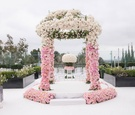 Ceremony arch on rooftop at The London West Hollywood pink and white roses on raised stage seating