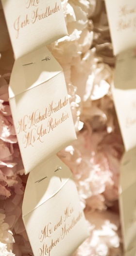 Wedding reception envelope escort cards, names in gilt calligraphy pinned to white, pink peonies