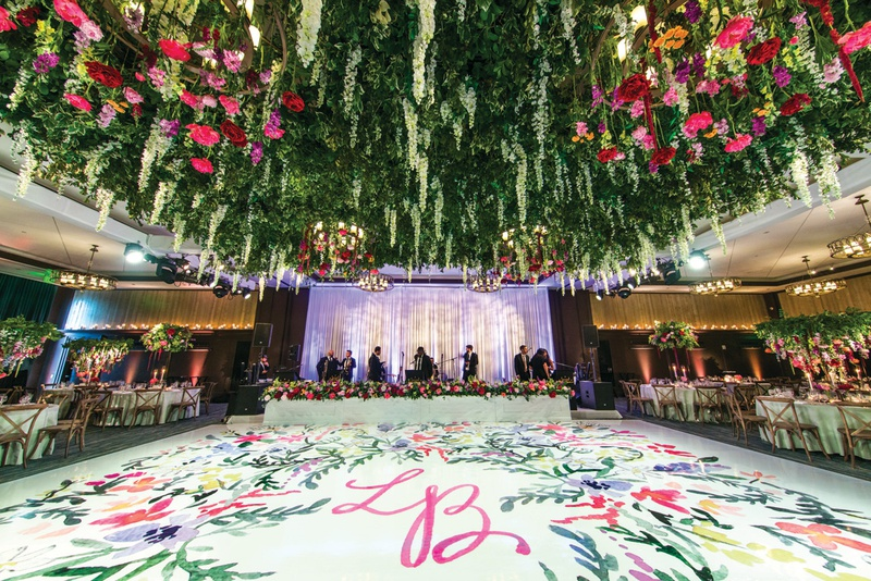 white dance floor painted with floral watercolor and pink initials, lush floral ceiling installation