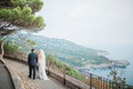 bride and groom walking along pathway showing the coast of capri