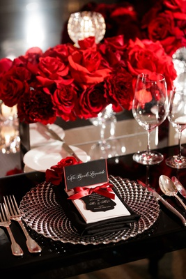 wedding reception place setting rose flowers in mirror box black table charger red border black card