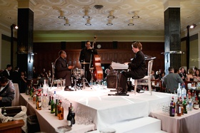 Wedding cocktail hour with cello player, drummer, and keyboardist behind bar, The Standard Club