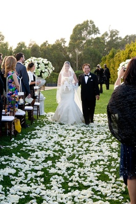 White rose petals on grass lawn and candles on shepherd hooks