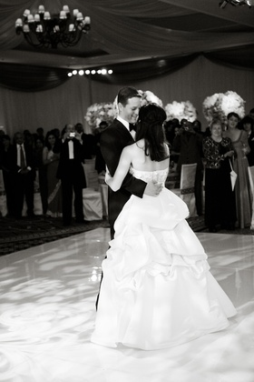 Black and white photo of bride in pick-up skirt first dance