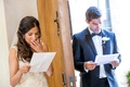 Bride puts hand up to mouth and groom smiles as read notes on opposite sides of door