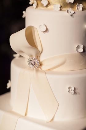 White wedding cake with top golden layer, fondant ribbon, and rhinestone pin, small fondant flowers