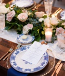 wedding reception tablescape wood table runner pink flowers greenery blue white chinoiserie china