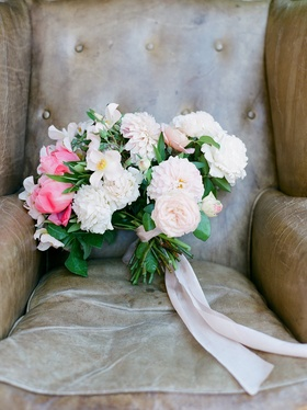 Green stems tied with pink ribbon pink peony ranunculus garden rose and bay leaf leather chair