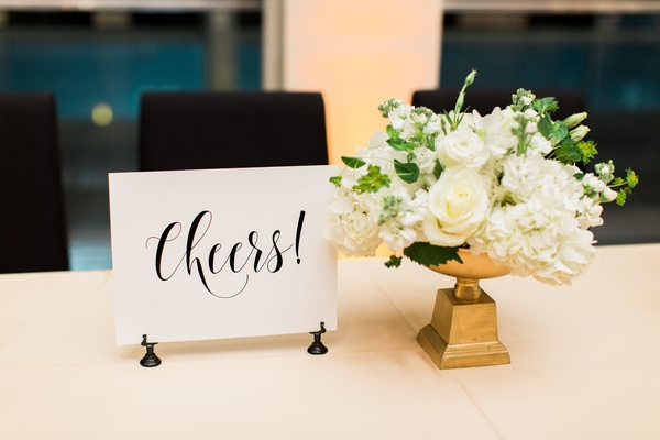 """cheers!"" sign next to small white floral arrangement on gold base"