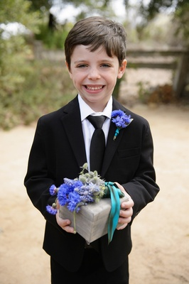 Boy smiling in suit with blue and purple flower ring box