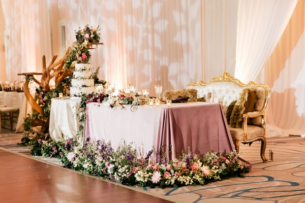 wedding reception ballroom sweetheart table gold antique settee purple linen greenery driftwood cake