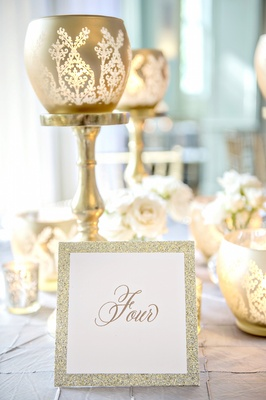 Gold calligraphy table number with glitter border