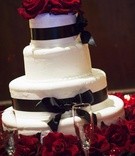 White wedding cake decorated with black satin ribbon and red roses