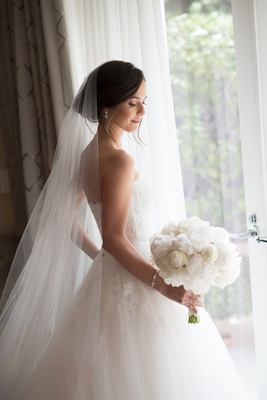 Bride in strapless Monique Lhuillier ball gown and veil with white peony bouquet updo natural makeup