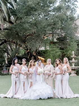bride in ines di santo wedding dress with ruffles, bridesmaids in dress me pretty neutral tones