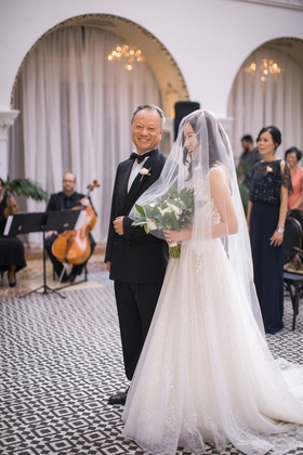 asian bride and father smiling at the end of walking down the aisle, bride in blusher veil