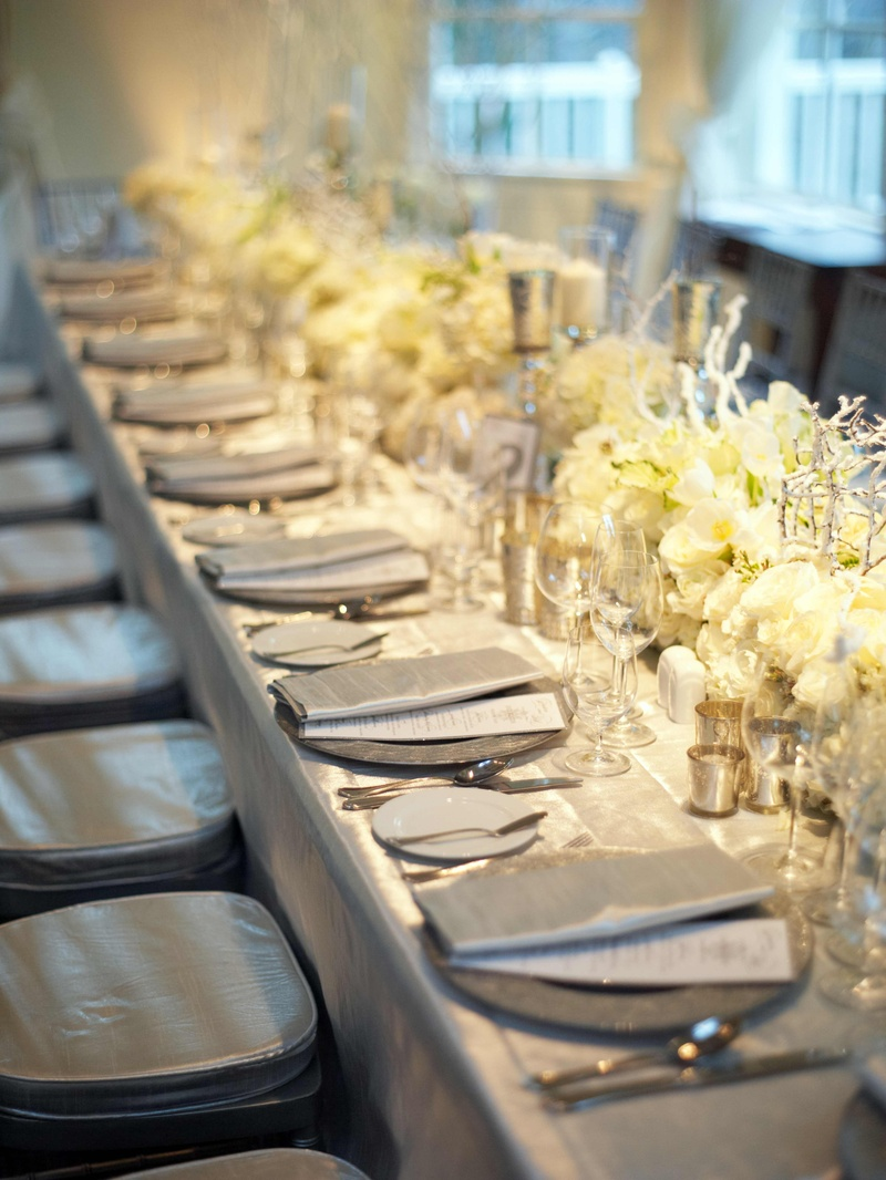 Silver reception table with white floral arrangements