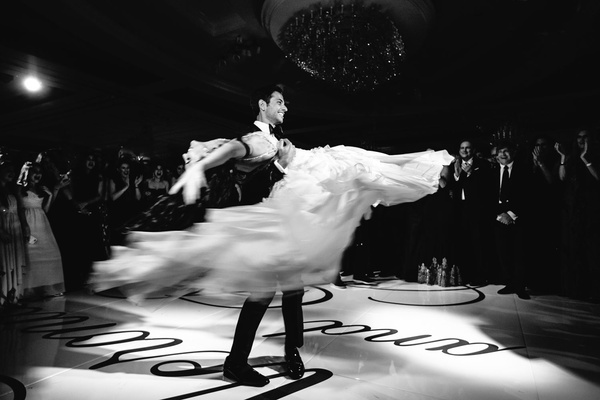black and white photo of bride and groom performing first dance at wedding on custom dance floor