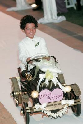 Cute little boy driving car down aisle