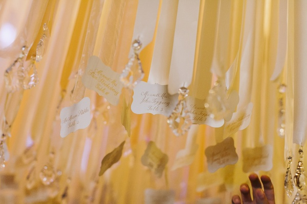 Whimsical seating card display hanging from ribbons
