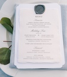 blue-grey napkin and linens, grey wax seal on menu