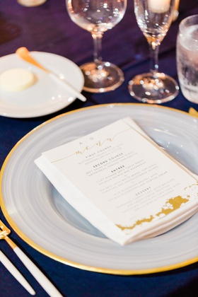 wedding menu card with gold calligraphy on white charger plate with gold rim matching flatware fork
