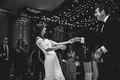 Black and white photo of bride and groom first dance Marchesa dress twinkle lights garlands