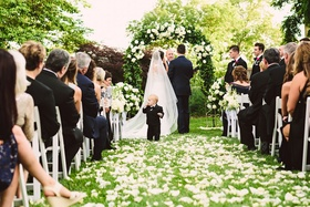 Outdoor wedding ceremony greenery arch flower ring bearer in little suit at front of ceremony space
