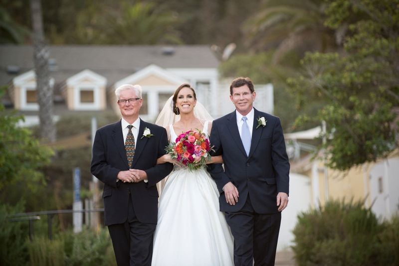 bride walks down aisle with father and stepfather at beach wedding