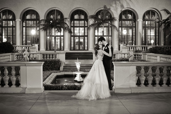 Black and white photo of bride kissing groom at wedding Anne Barge dress The Breakers Palm Beach